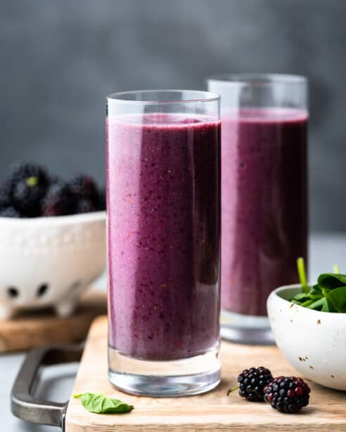 Blackberry Green Smoothie in a glass with fresh spinach and blackberries on the side.