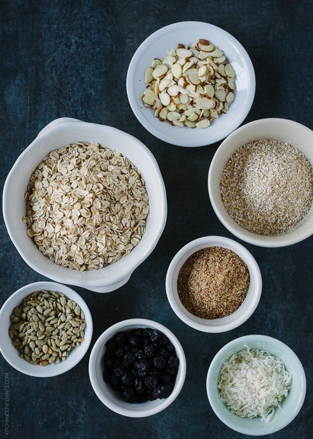 White bowls filled with ingredients to make homemade muesli, like oats, dried blueberries, and flaxseed meal.