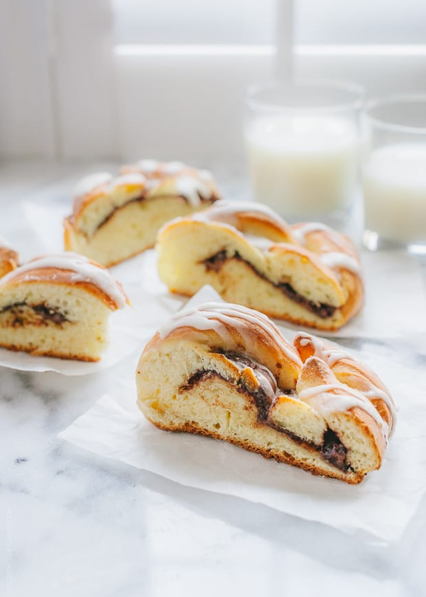 Slices of Braided Nutella Bread with glasses of milk nearby.