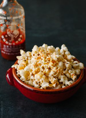 A red bowl filled with spicy sriracha popcorn.