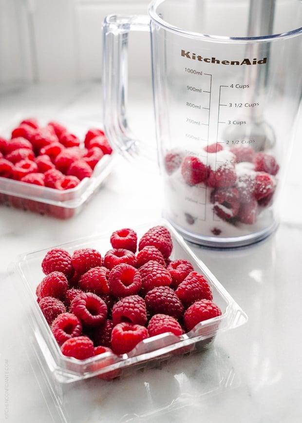 Fresh raspberries on a white surface.