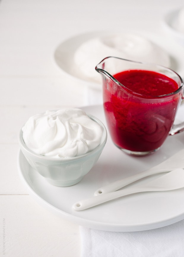 Raspberry sauce in a small glass pitcher and a bowl of fresh whipped cream.