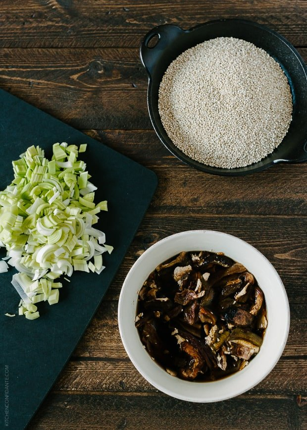 A bowl of quinoa, a bowl of porcini mushrooms, and chopped leeks on a wooden surface.