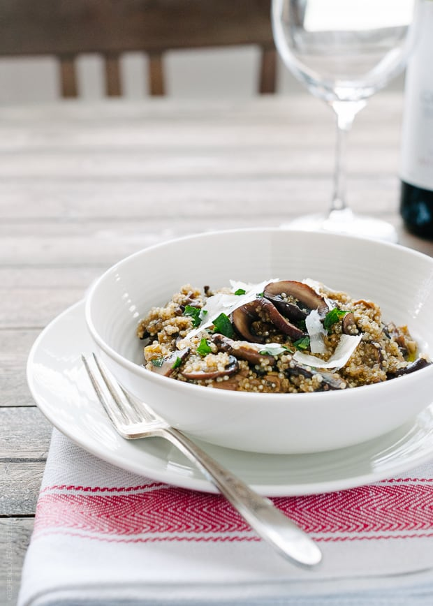 A white bowl on a table filled with Mushroom Quinoa Risotto.
