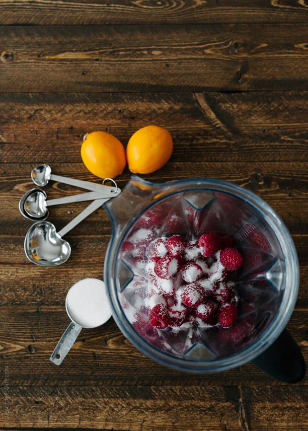 A bowl of fresh raspberries and sugar surrounded by measuring spoons and lemons.