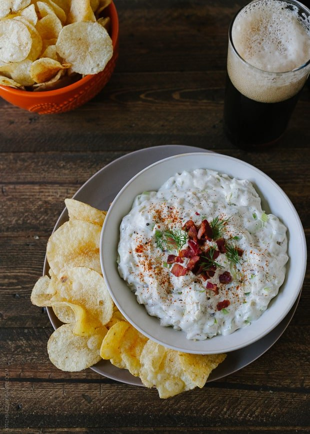 A bowl of Bacon Leek Dip, potato chips, and a glass of beer.
