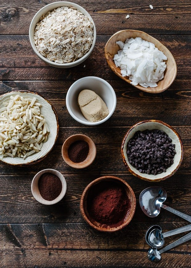 Bowls of oats, slivered almonds, coconut, and more ingredients to make homemade granola arranged on a wooden surface.