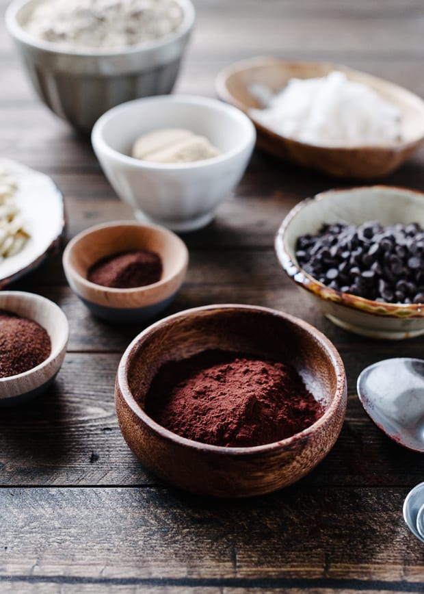 Cocoa powder and espresso powder in wooden bowls on a wooden surface.