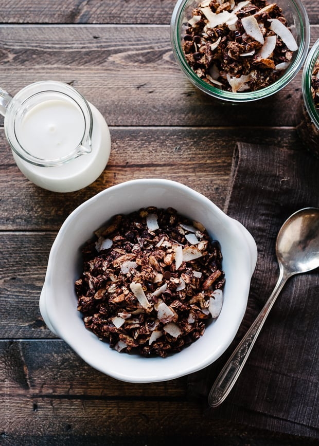 Milk, a spoon, and a bowl of homemade granola on a wooden surface.