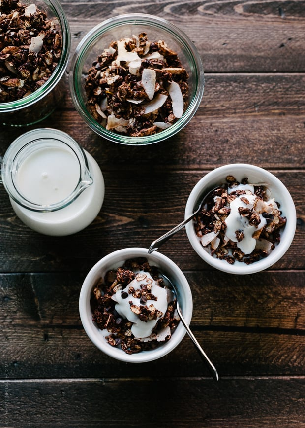 Small white bowls of Mocha Coconut Granola on a wooden surface.