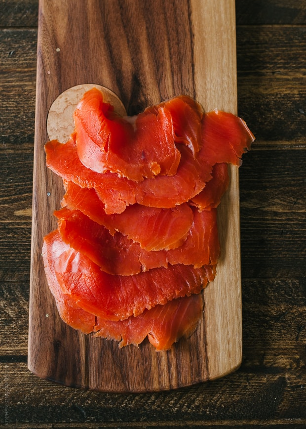 Slices of smoked salmon on a wooden serving board.