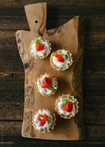 Five smoked salmon appetizer bites on a wooden serving board.