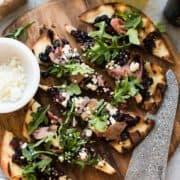 Caramelized Onion, Feta & Serrano Ham Flatbread sliced on cutting board.