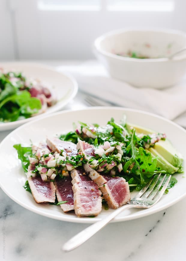 Seared Ahi Tuna over a salad on a white plate.