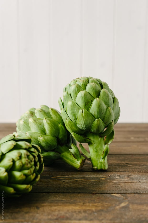 Artichokes on a wooden surface.