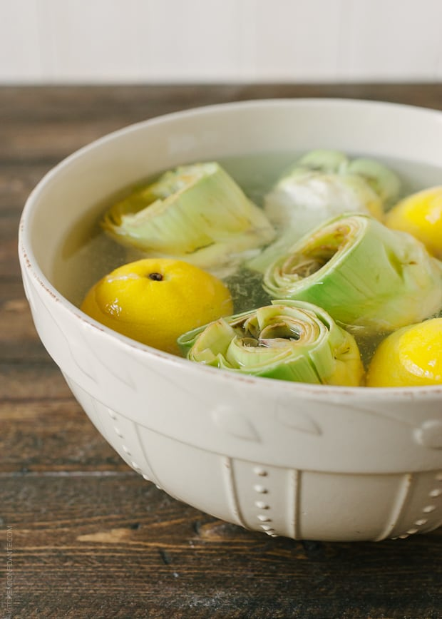 Artichokes soaking in water with lemons.