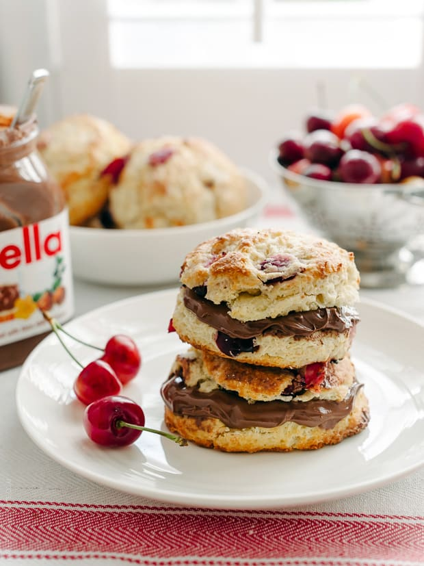Cherry Nutella Scones split open, spread with Nutella, and stacked on a white plate.