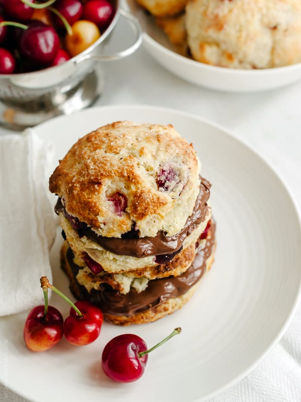 Cherry Nutella Scones on a white plate with fresh cherries.