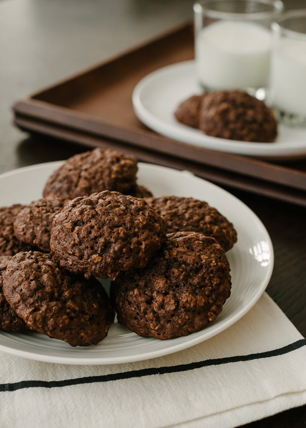 A white plate filled with chocolate oatmeal cookies.