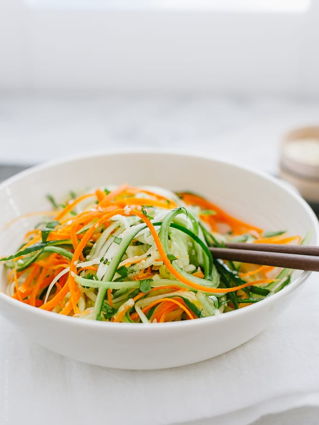 Julienned carrots and cucumbers tossed with dressing for an Asian Cucumber Salad.