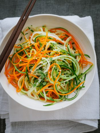 A white bowl filled with Asian Cucumber Carrot Slaw.