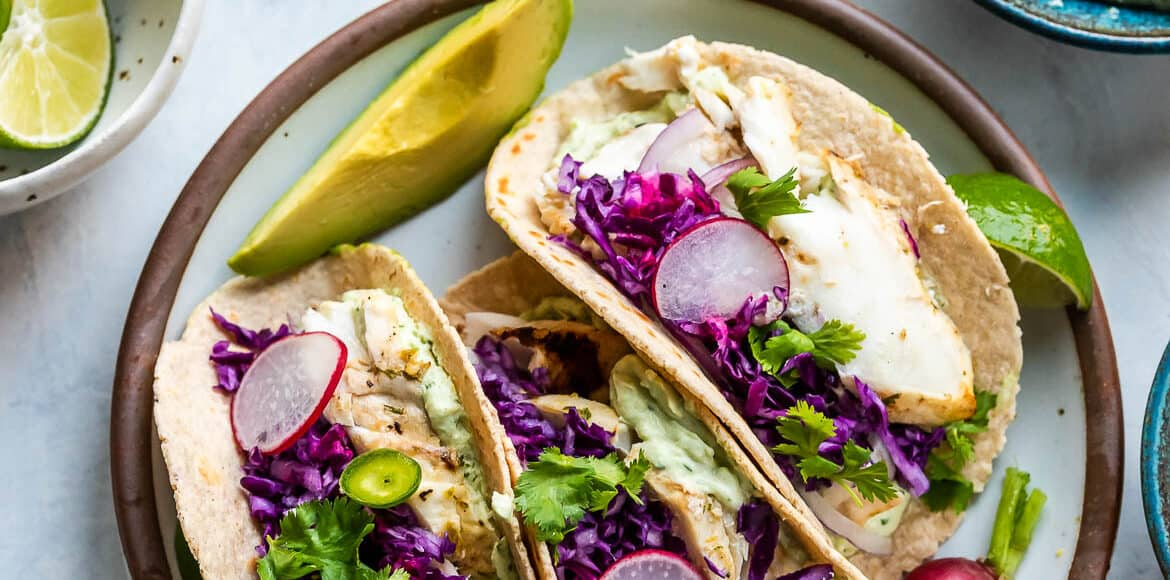 Grilled Fish Tacos with Avocado-Cilantro Sauce on a plate garnished with red cabbage, radishes and jalapeño.