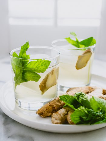 Two coconut water coolers garnished with mint and ginger.
