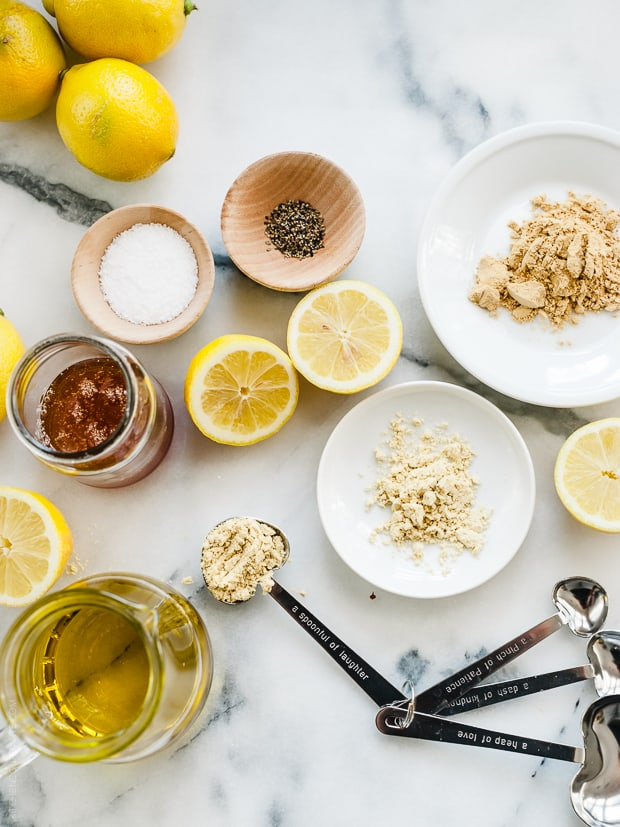 Honey, spices, and lemons arranged on a marble surface.