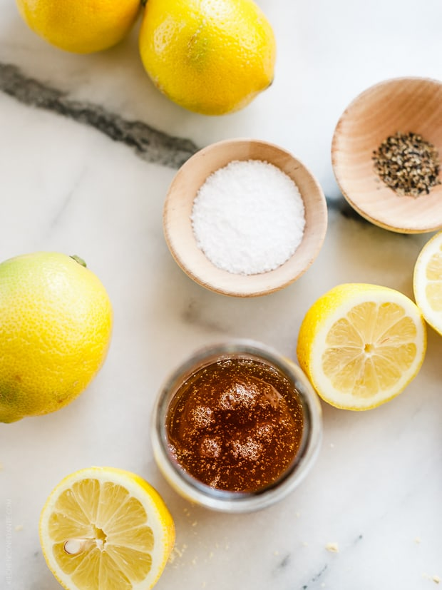 Spices and halved lemons on a marble surface.
