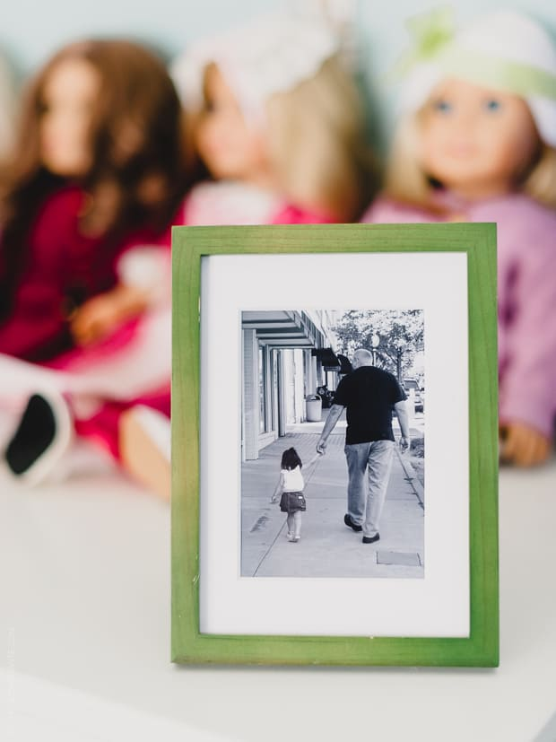 A framed photo of a young girl and her grandfather holding hands as they walk down a sidewalk.