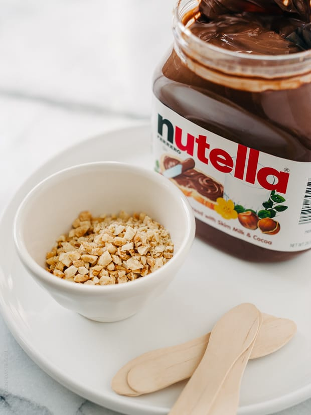 A jar of Nutella, a dish of chopped nuts and popsicle sticks.