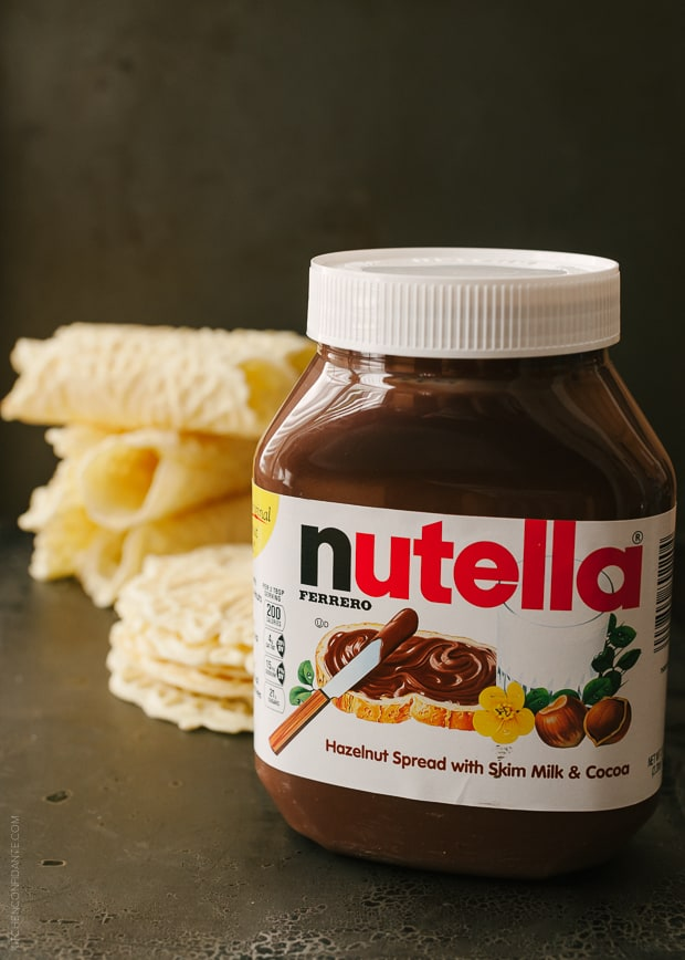 A jar of Nutella with pizzelle in the background.