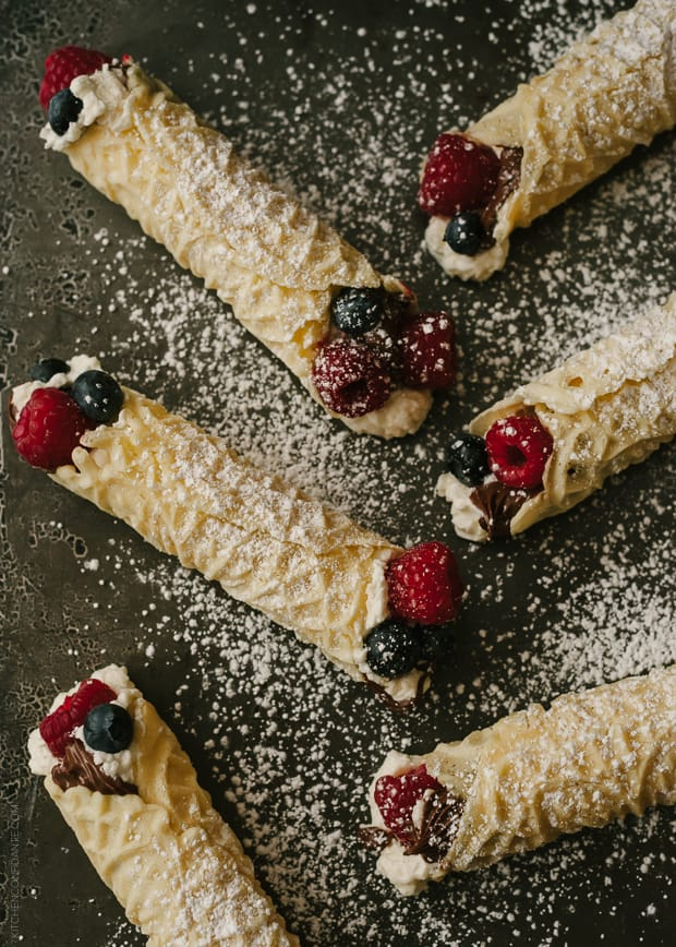 Rolled pizzelle cookies filled with whipped cream, berries, and Nutella.