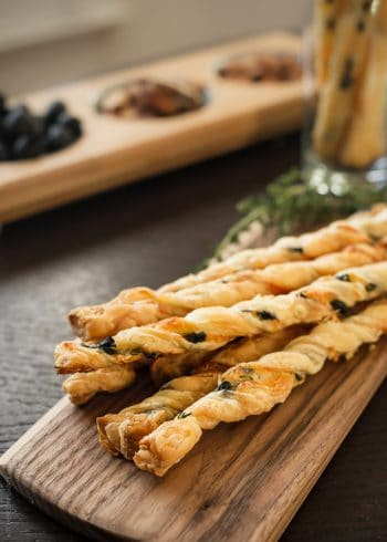 Olive Cheese Straws arranged on a serving board.