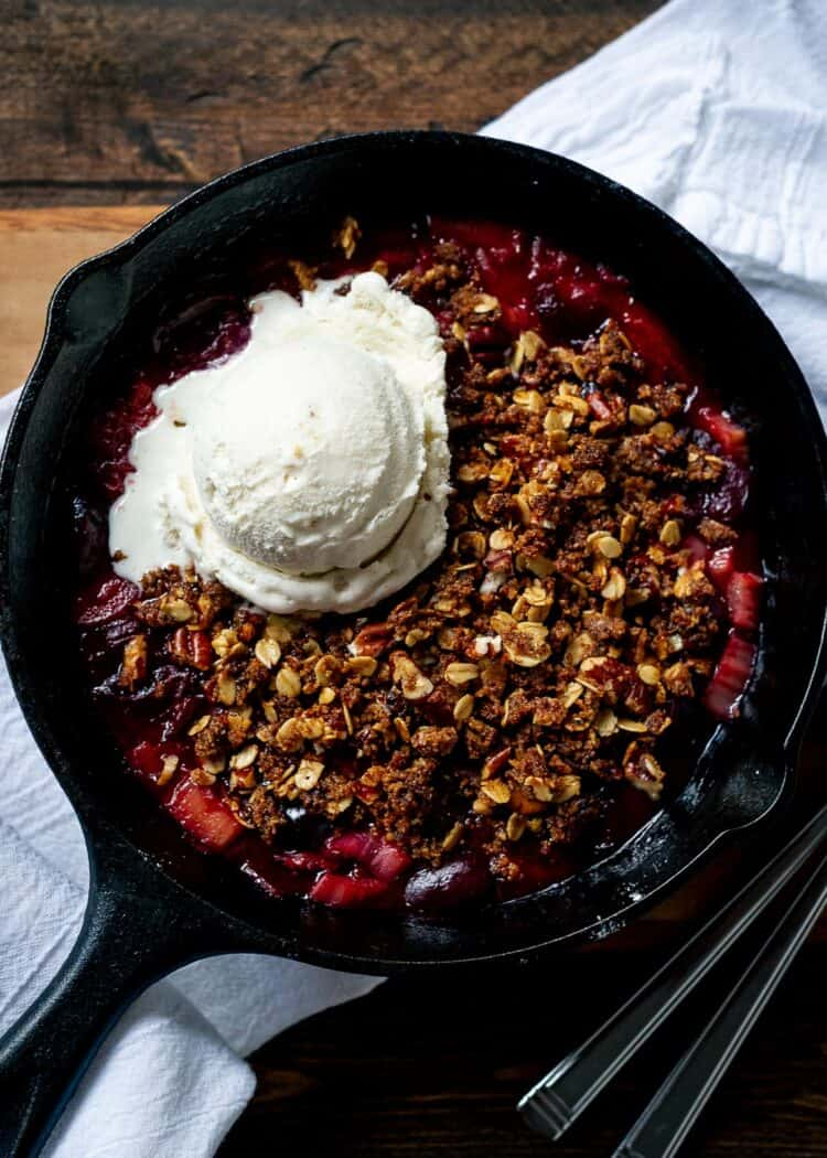 Stovetop Rhubarb-Cherry Crisp with vanilla ice cream in a skillet.