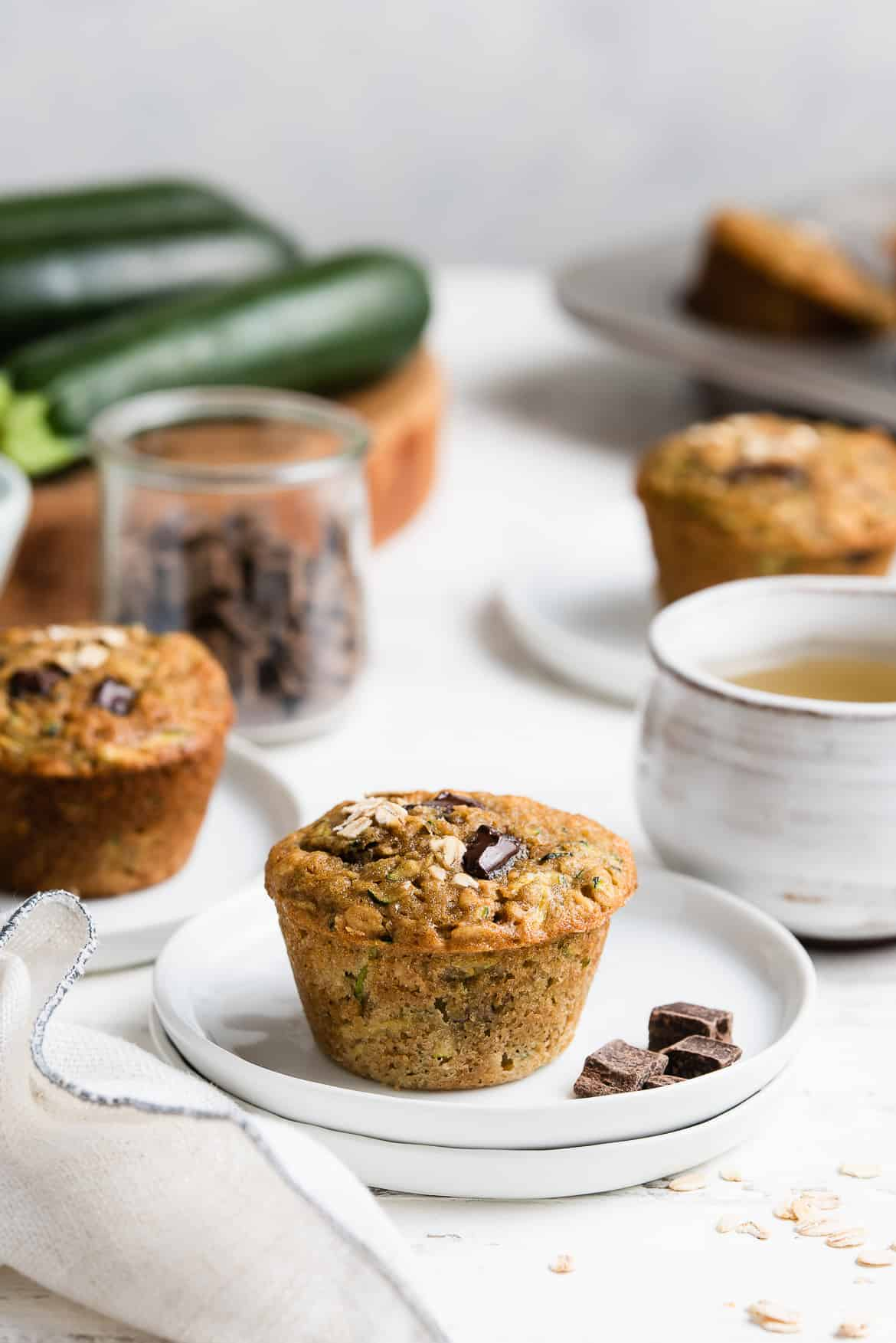 Zucchini Oat Chocolate Chunk Muffins on small white plates with a cup of tea.