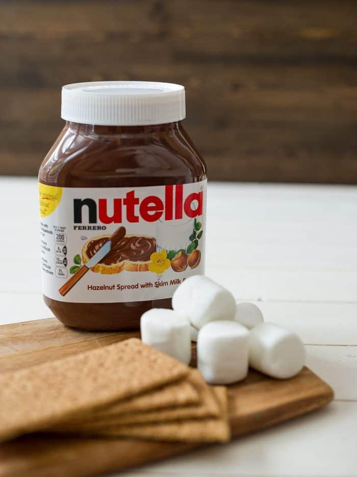 A jar of chocolate hazelnut spread, graham crackers, and marshmallows.