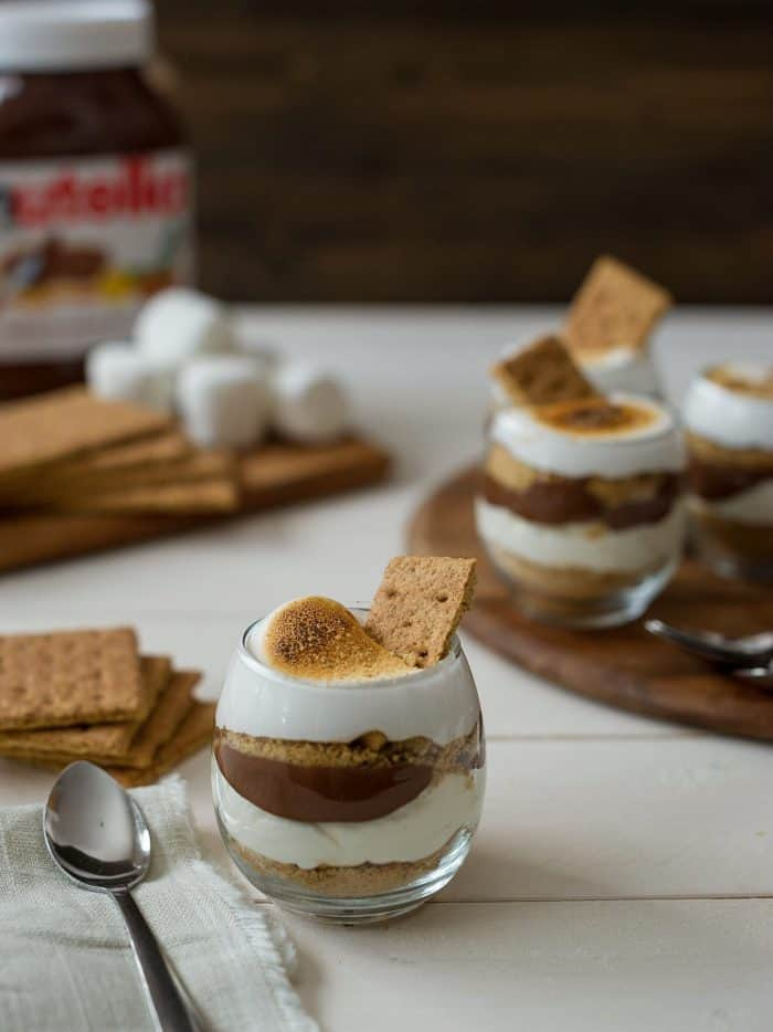 A layered Nutella S'mores Parfait served with a spoon and surrounded by graham crackers.