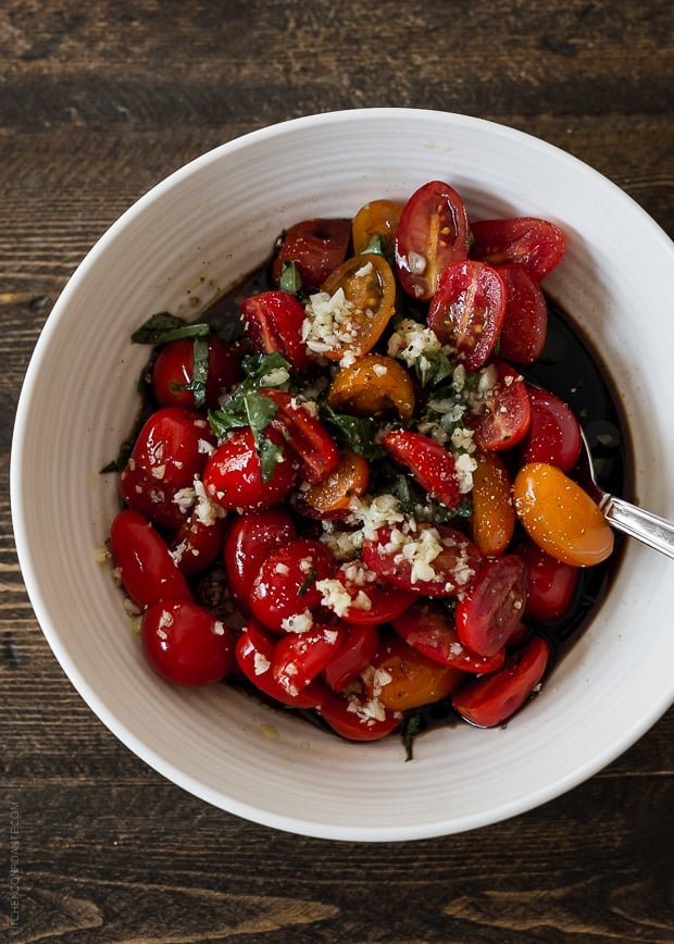 Sliced cherry tomatoes in a white bowl covered with balsamic vinegar and a garlic olive oil.
