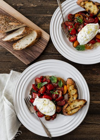 Heirloom tomatoes on a white plate topped with burrata and surrounded with toasted baguette slices.