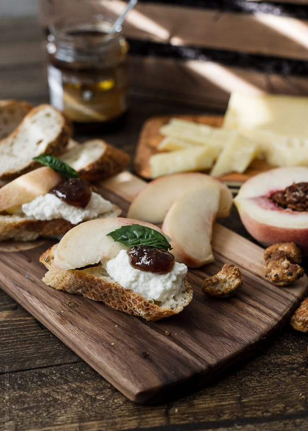 Baguette slices topped with fruit and cheese on a cheese board.