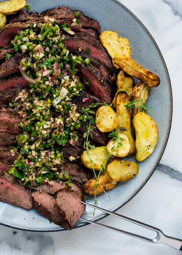 Sliced grilled flank steak surrounded by grilled fingerling potatoes and topped with chimichurri sauce.
