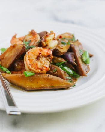 An eggplant and shrimp stir fry served on a white plate.