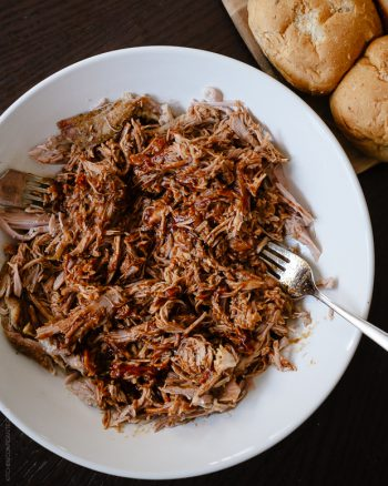 Slow Cooker Stout Pulled Pork shredded on a white serving plate.