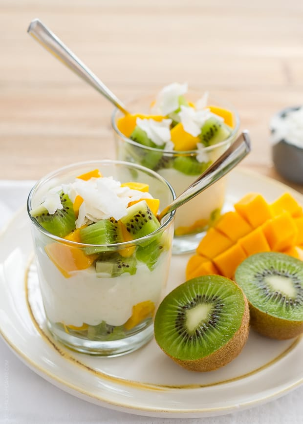 Rice pudding layered in glasses with coconut flakes, chopped kiwi and chopped mango