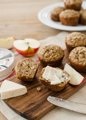 Muffins halved and spread with a creamy cheese on a wooden serving board.