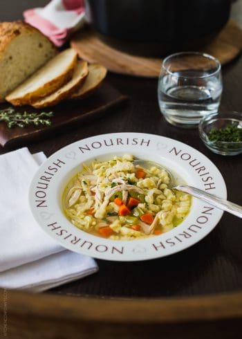 "Chicken and Herb Spaetzle Soup served in a bowl with the word, ""Nourish"" around the rim."