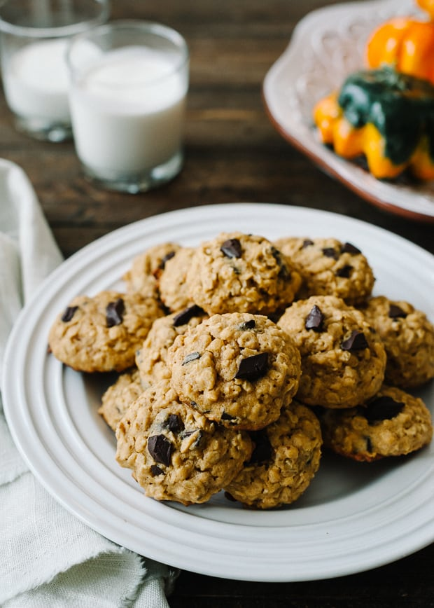 A large stack of Pumpkin Chocolate Chip Oatmeal Cookies on a white serving plate.
