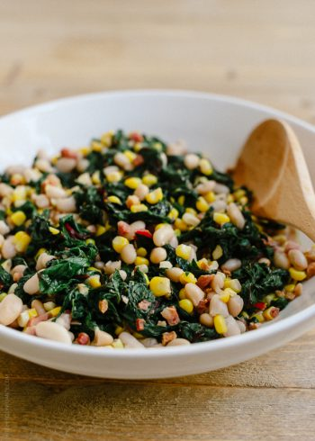 A white bowl filled with Swiss Chard with Pancetta, Corn and Cannelini Beans.