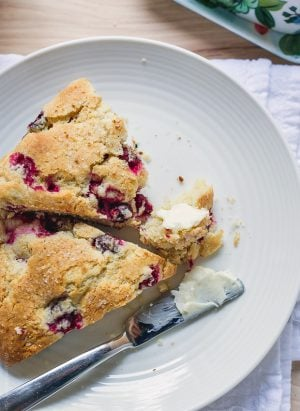 Two Make-Ahead Cranberry Scones on a white plate alongside a buttered knife.